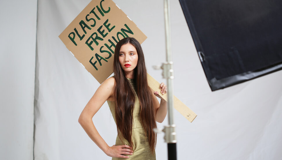 model holding plastic free fashion sign - data and technology is the future of sustainable fashion
